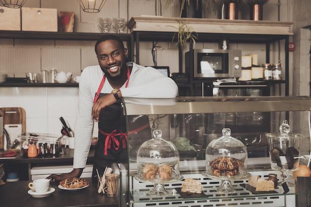 Glimlachend mannetje van afro het amerikaanse barista op het werk