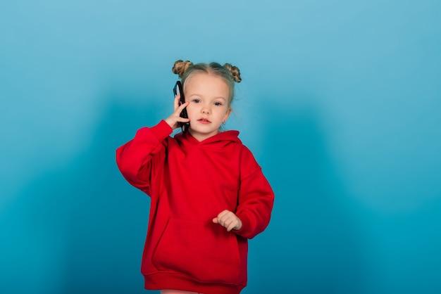 Glimlachend meisje aan de telefoon over blauwe achtergrond
