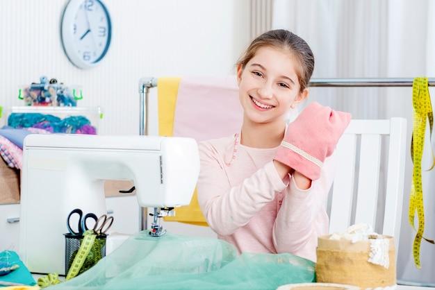 Glimlachend meisje dat bij de naaimachine werkt