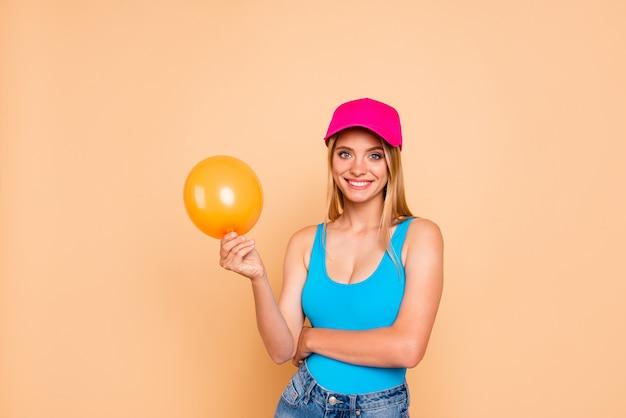 Glimlachend meisje dat casualclothes draagt die gele luchtballon houdt