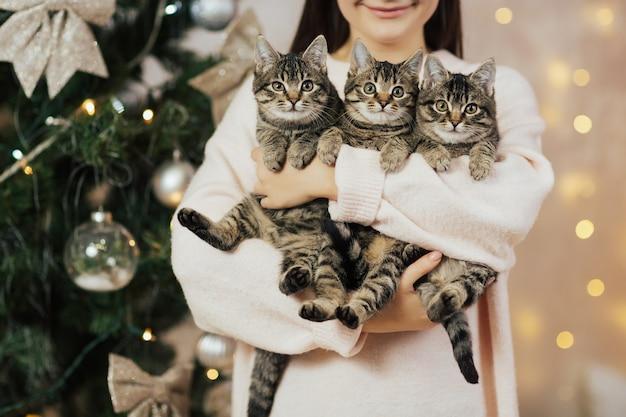 Glimlachend meisje dat drie zoete katjes houdt.