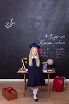 Glimlachend meisje dat een afstudeerpet van een meester draagt op school