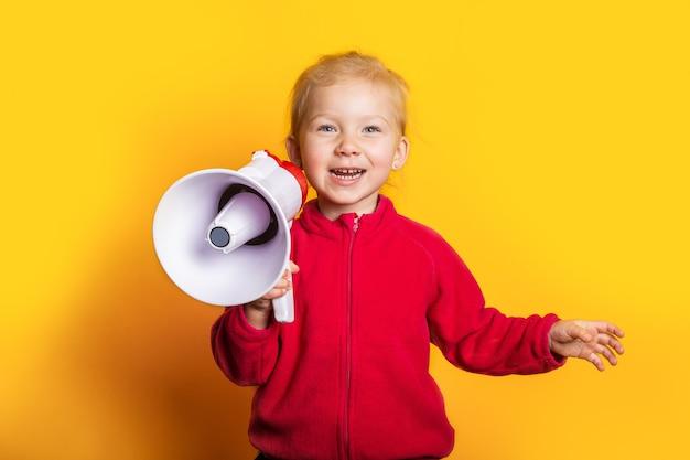 Glimlachend meisje dat een megafoon op een heldere gele achtergrond houdt.
