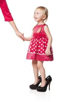 Glimlachend meisje dat grote schoenen draagt die de hand van haar moeder kantelen. geïsoleerd op witte achtergrond