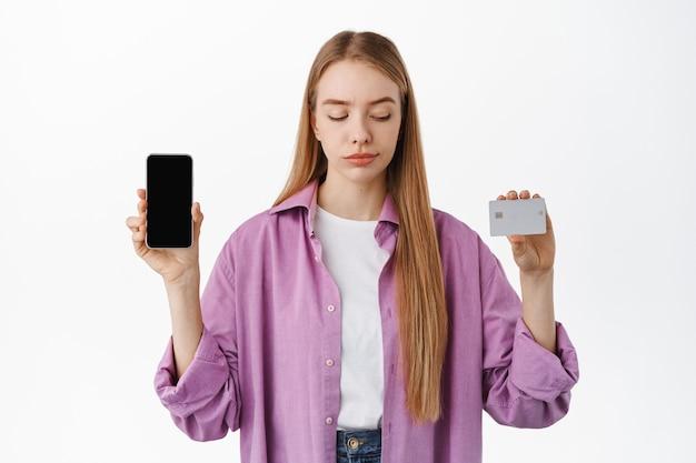 Glimlachend meisje dat het smartphonescherm laat zien, nadenkend naar de bankcreditcard kijkt, aan winkelen denkt, over een witte muur staat