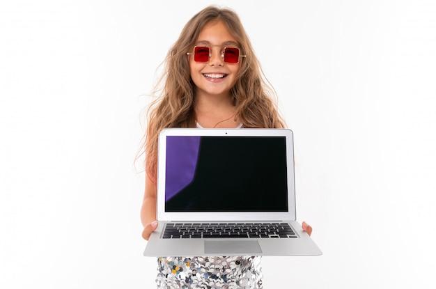 Glimlachend meisje dat in fonkelende kleding en vierkante rode zonnebril moderne laptop met het zwarte geïsoleerde scherm houdt