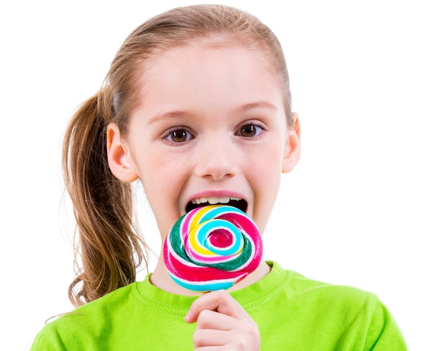 Glimlachend meisje dat in groen t-shirt gekleurd suikergoed eet - dat op wit wordt geïsoleerd