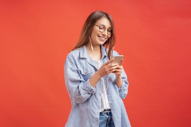 Glimlachend meisje dat in vrijetijdskleding en oortelefoons aan het scherm van de telefoon kijkt
