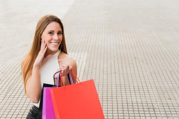 Glimlachend meisje dat met het winkelen zakken camera bekijkt