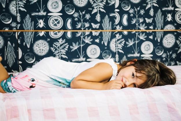 Glimlachend meisje dat op bed ligt