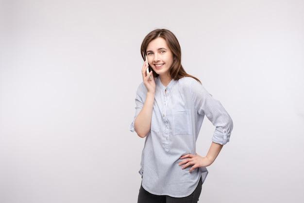 Glimlachend meisje dat op de telefoon spreekt. mooie jonge donkerbruine vrouw in toevallig overhemd en jeans die op de mobiele telefoon spreekt en bij camera glimlacht. isoleer op wit.