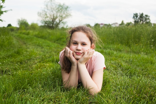 Glimlachend meisje dat op gras ligt en camera in park bekijkt