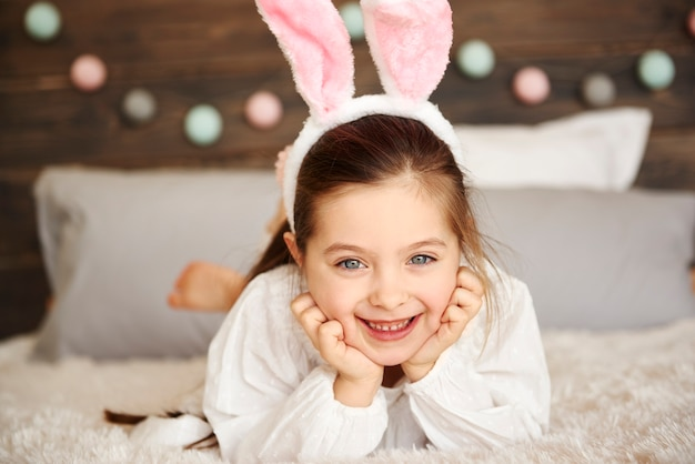 Glimlachend meisje dat op het bed ligt