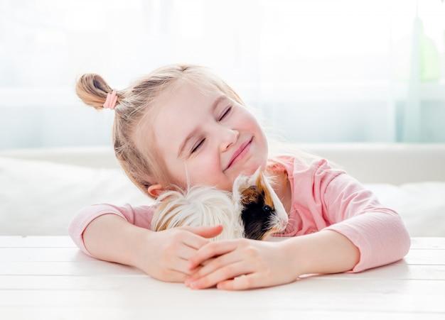 Glimlachend meisje dat proefkonijn koestert