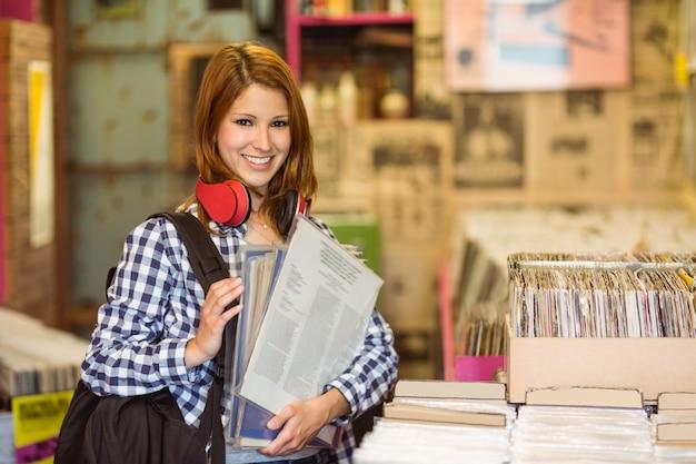 Glimlachend meisje dat sommige vinyls houdt