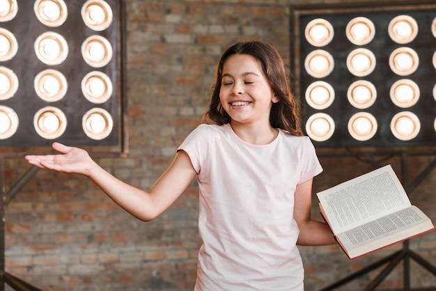 Glimlachend meisje dat tegen stadiumlicht presteert