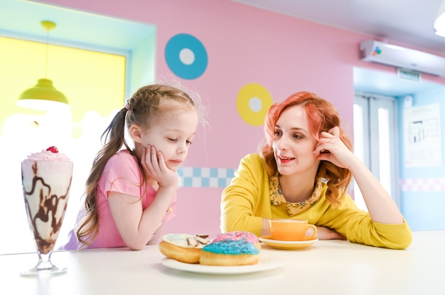 Glimlachend meisje dat van zijn ongezonde lunch met mamma geniet. diëten, eten, levensstijl