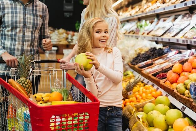 Glimlachend meisje dat voor kruidenierswinkels winkelt