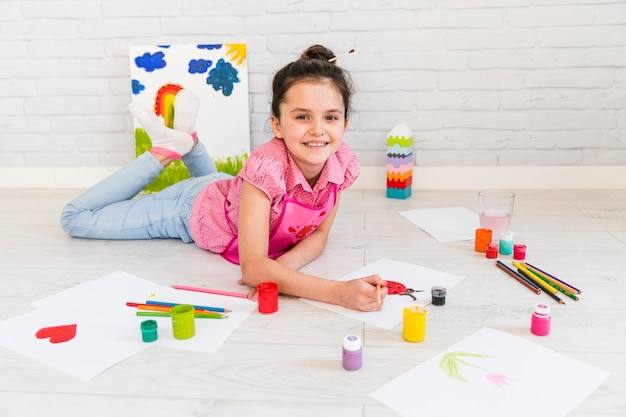 Glimlachend meisje die bij vloer het schilderen met verfborstel op witboek liggen