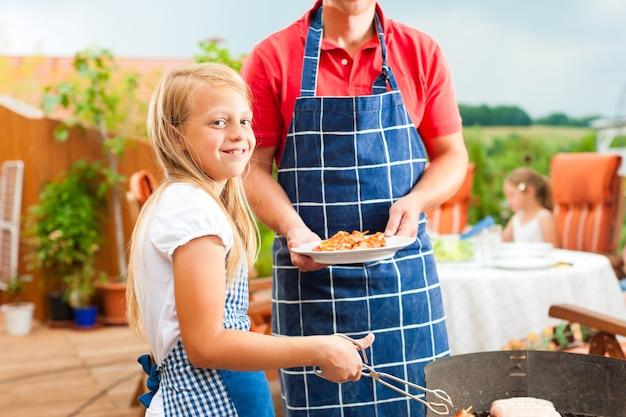 Glimlachend meisje die de familiebarbecue voorbereiden