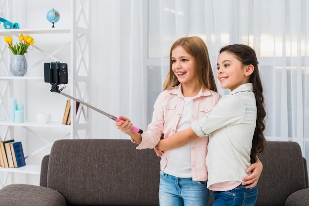 Glimlachend meisje die haar vriend omhelzen die selfie op slimme telefoon nemen