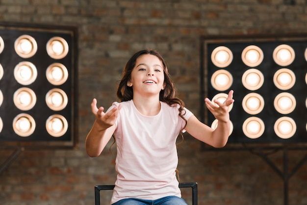 Glimlachend meisje die in studio met stadiumlicht op de achtergrond handelen