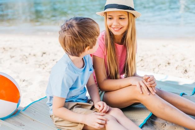 Glimlachend meisje die jongen gelukkig op kust bekijken