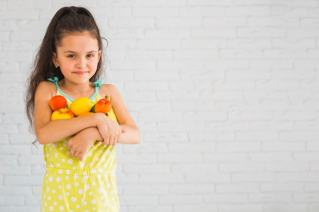 Glimlachend meisje die kleurrijke vruchten in haar twee wapens houden