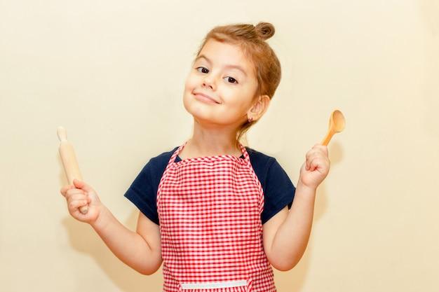 Glimlachend meisje die met chef-kokschort houten deegrol en een lepel op beige achtergrond houden