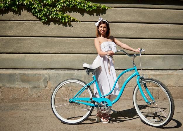 Glimlachend meisje die met een blauwe uitstekende fiets weg op een muurachtergrond kijken met groene klimplant zonnige dag