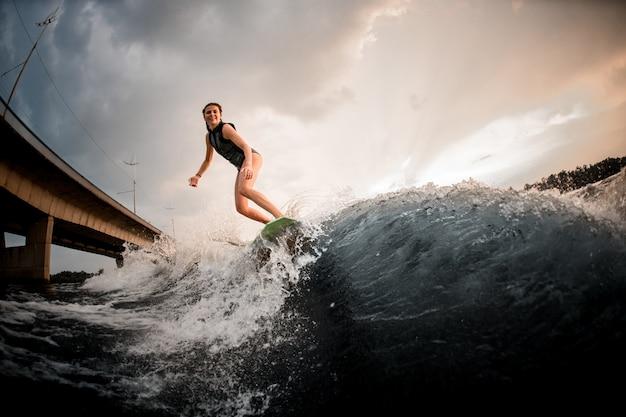 Glimlachend meisje die op wakeboard op de rivier op de achtergrond van de brug berijden