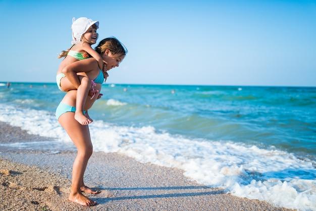 Glimlachend meisje draagt haar kleine charmante zusje op haar rug terwijl u ontspant op het strand op een warme zomerdag.