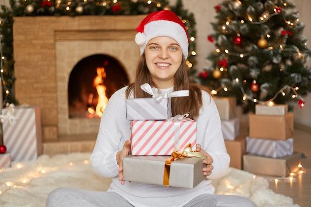 Glimlachend meisje geven kerstcadeautjes thuis, geschenkdozen in handen houden zittend op de vloer