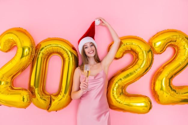 Glimlachend meisje heft glas champagne op in kerstmuts gouden luchtballonnen nieuwjaarsfeest