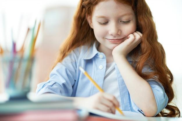Glimlachend meisje het afronden van haar huiswerk