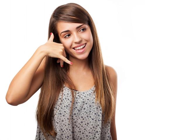 Glimlachend meisje het maken van bel me gebaar