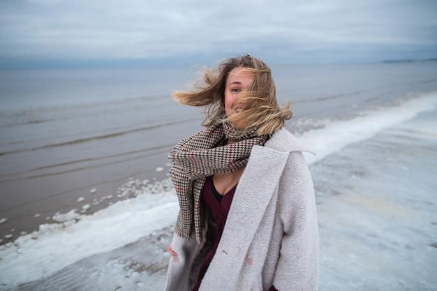 Glimlachend meisje in de bordeauxrode jurk en jas op de achtergrond van de winterzee. portret van een vrouw op zee, winderig sneeuwweer, koud sfeerbeeld.