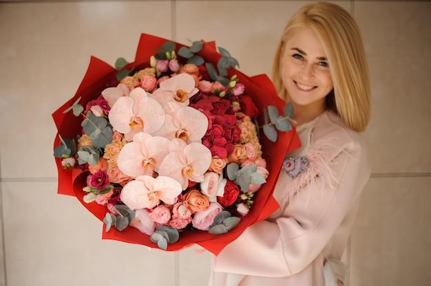Glimlachend meisje in de jas met een boeket van roze en rode bloemen versierd met groen
