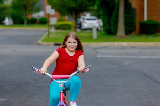 Glimlachend meisje in de zomerkleren fietsten in het park op een stad
