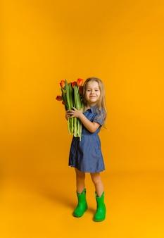 Glimlachend meisje in een blauwe jurk en rubberen laarzen houdt een boeket rode tulpen op een gele muur met een kopie van de ruimte