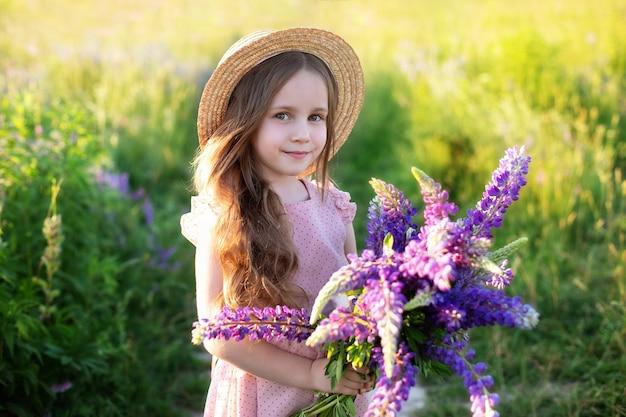 Glimlachend meisje in een strohoed en met boeketbloemen een kindmeisje in een veld met lupines kind met een boeket in de zomerweide