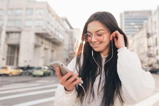 Glimlachend meisje in een witte casual kleding en zonnebril, luistert naar muziek in de koptelefoon, kijkt naar de smartphone in haar hand en lacht