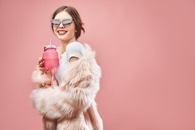 Glimlachend meisje in faux roze bontjas zwarte korte broek witte top en zonnebril houdt roze drank met cl...