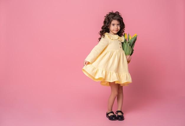 Glimlachend meisje in gele jurk op roze studio