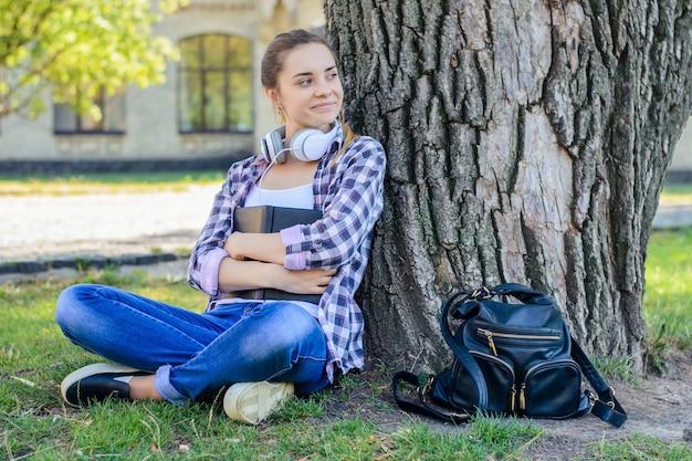 Glimlachend meisje in geruit overhemd en spijkerbroek zittend op het gras met boek in handen