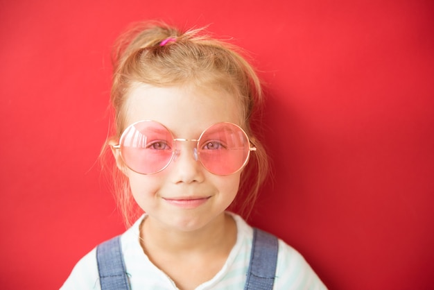 Glimlachend meisje in grote ronde roze glazen op rode achtergrond