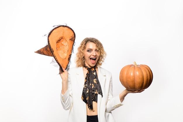 Glimlachend meisje in heksenhoed met pompoen happy halloween voorbereiding halloween vakantie vrouw heks