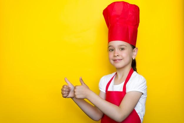 Glimlachend meisje in het kostuum van een rode chef-kok en het tonen van duim op gebaar op geel