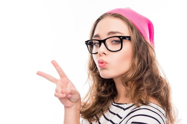Glimlachend meisje in hoed en bril met twee vingers en steenbolk