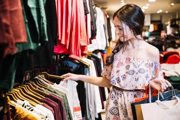 Glimlachend meisje in kleding winkel kiezen